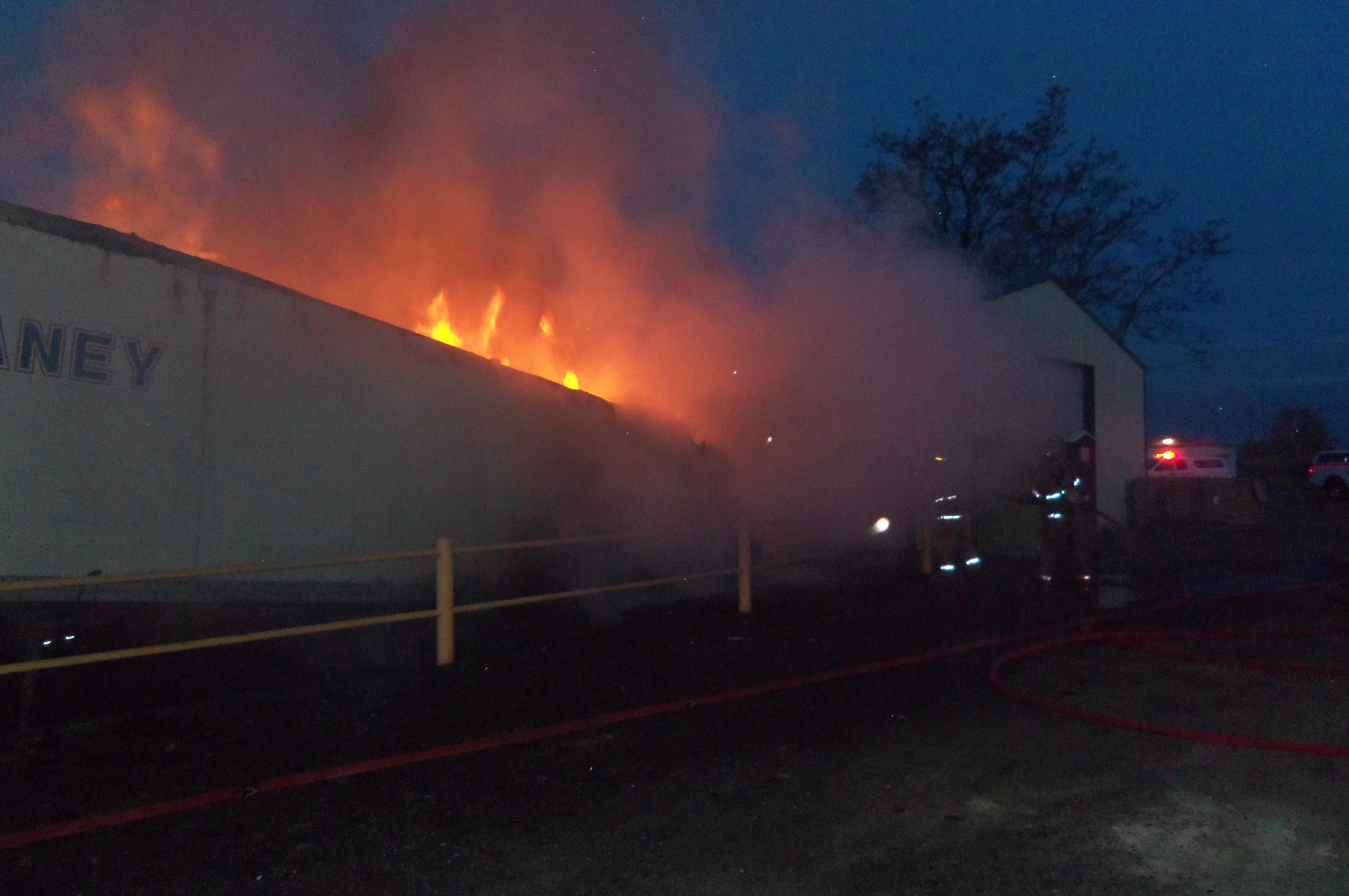 Trailer on fire next to building